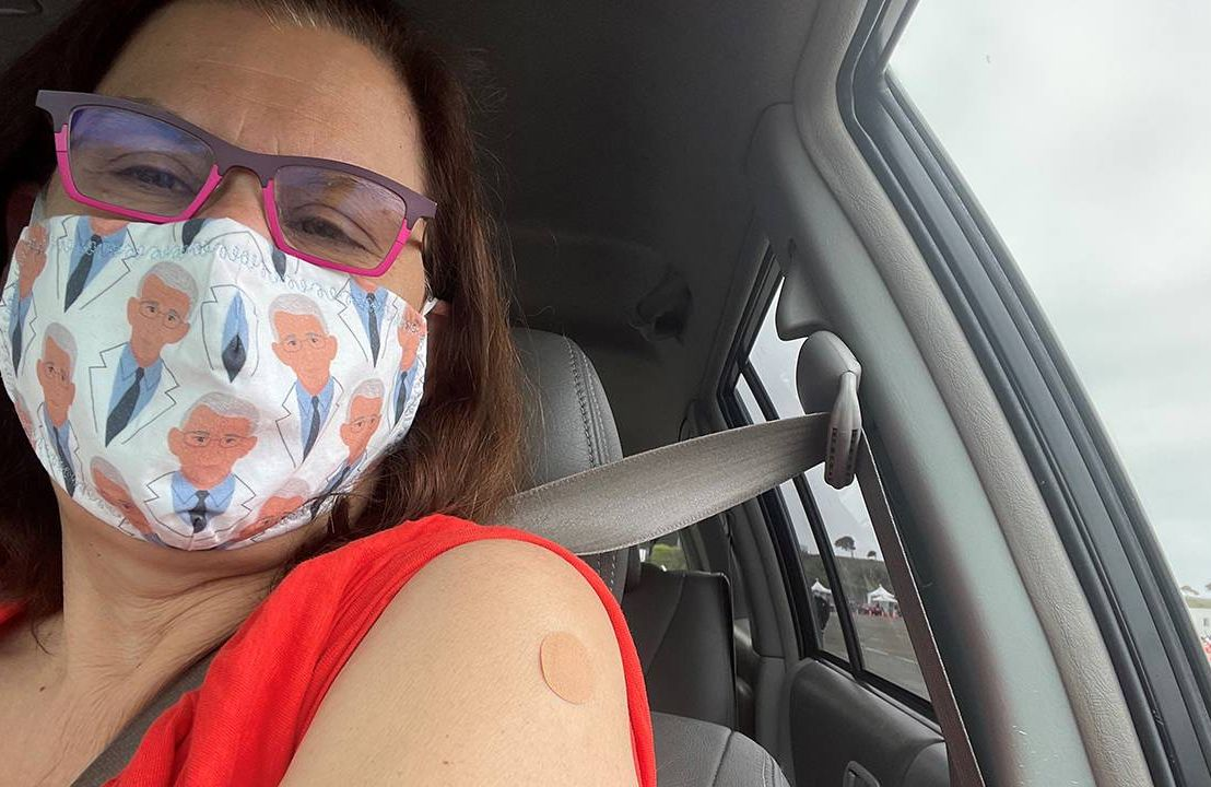 A woman wearing a face mask in her car displays her vaccine bandaid. Which vaccine to get, COVID-19 vaccine, Next Avenue