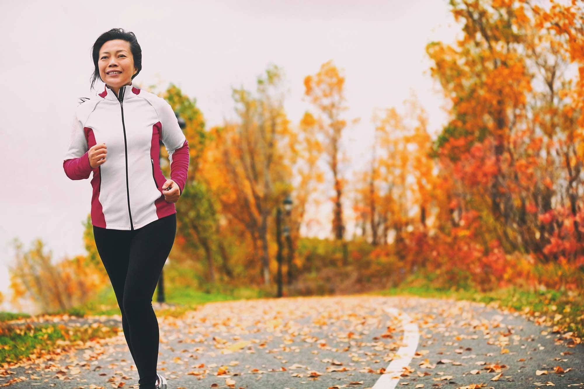 A woman runs on a running path with trees in fall colors behind her.