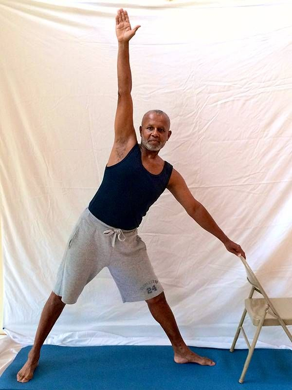 Man standing in triangle pose, yoga, Next Avenue