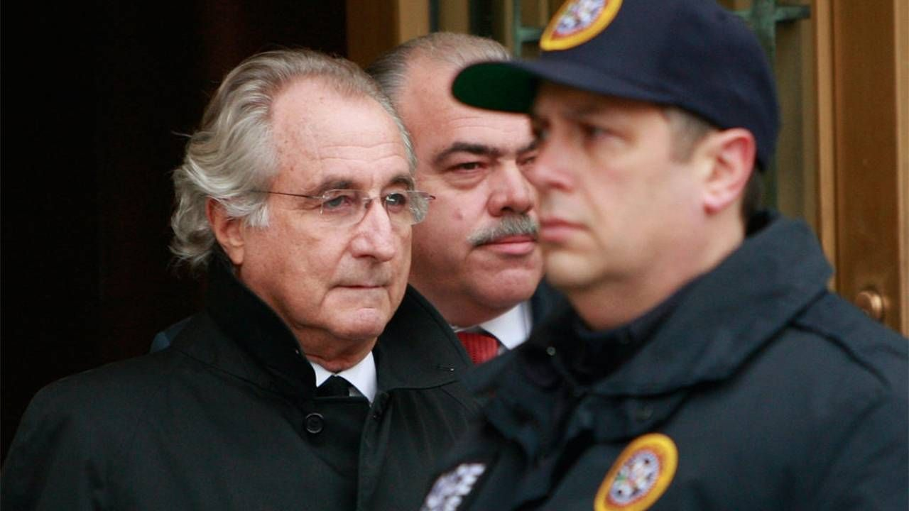 Bernie Madoff being escorted by two police officers. Madoff Talks, small investors, Next Avenue