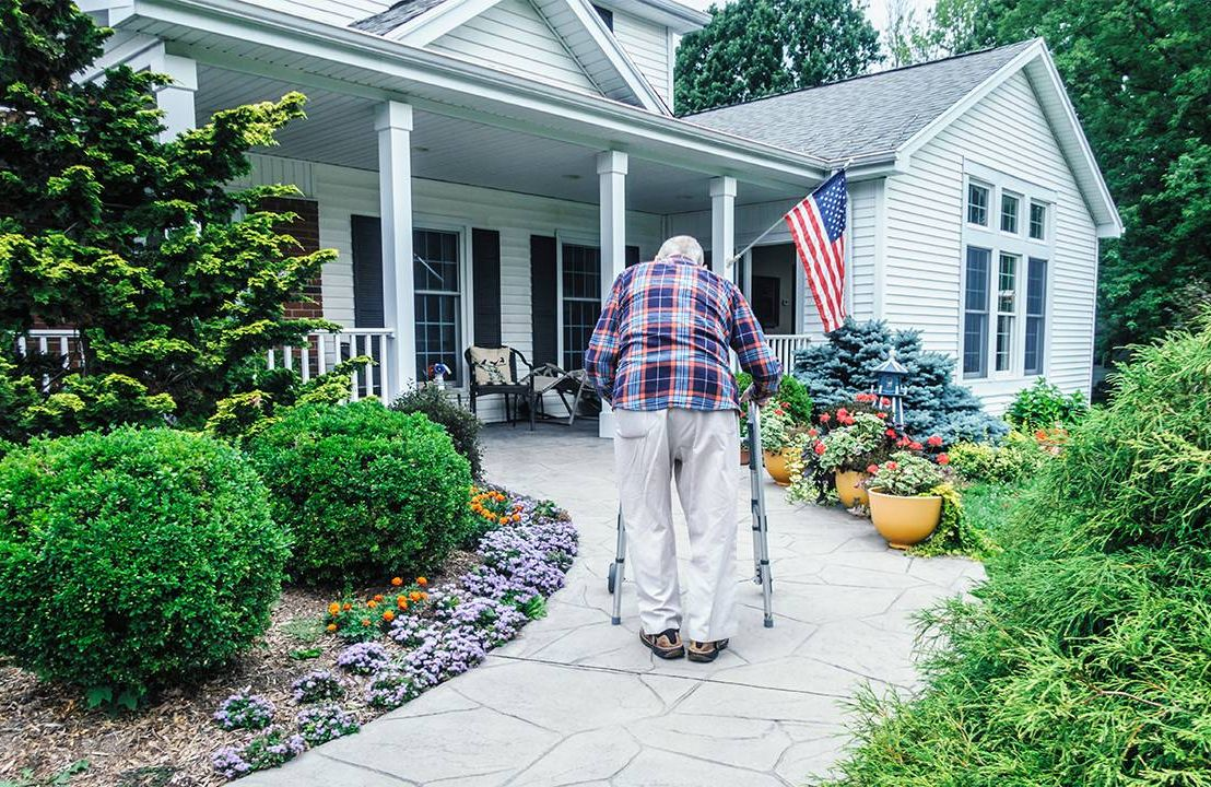 An older man walking up a ramp to his front door with a walker. Aging in place plan, age in place, Next Avenue