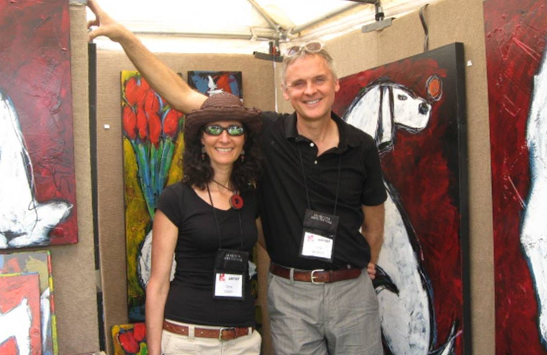 The author and her husband posing at their art booth in front of paintings. Art Festivals, Art, Next Avenue