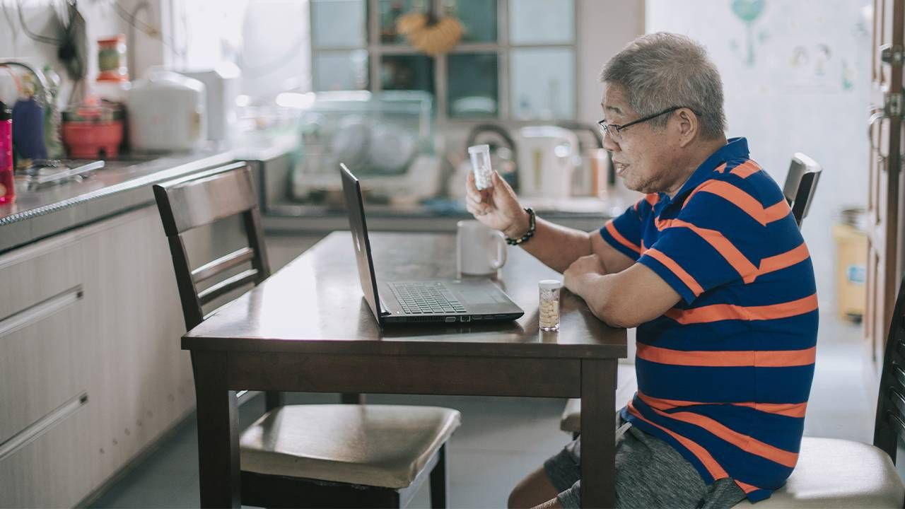 A midle aged man sitting at table on a telehealth doctor appointment. Ask the doctor, health, Next Avenue