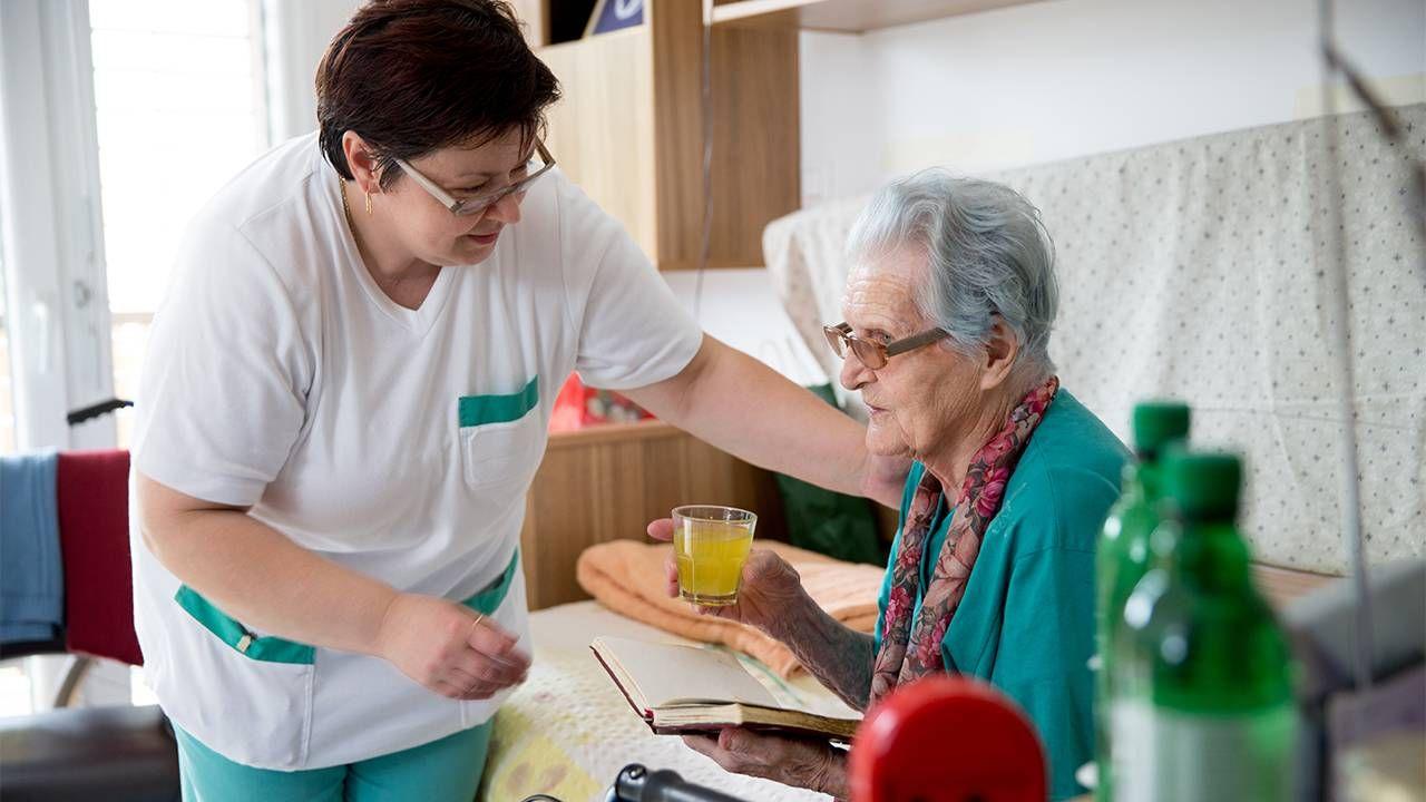 A professional caregiver assisting an older adult. Caregiving, caregiver, Next Avenue