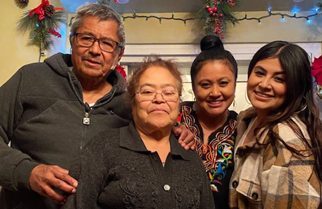 A multigenerational family smiling during the holiday season.