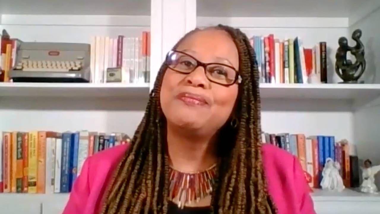 Michelle Singletary wearing a pink blazer in front of a bookshelf. Money, finances, Singletary's, Next Avenue