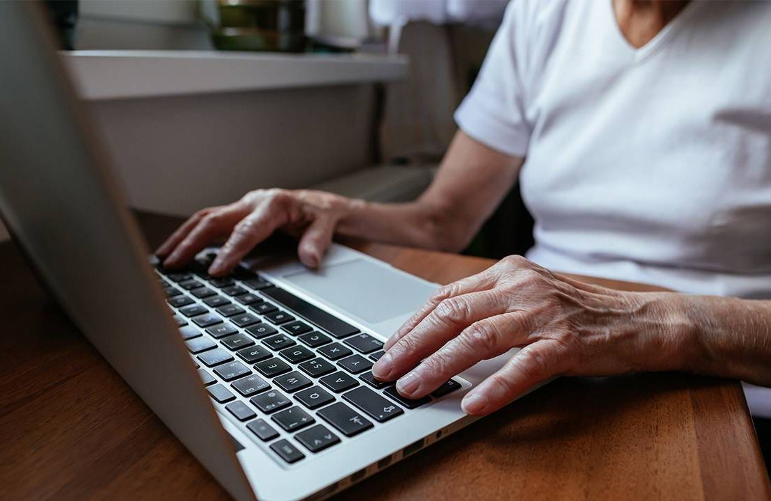 A closeup of an older woman typing on a laptop. Internet, digital divide, Next Avenue