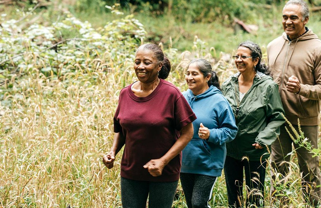 Group of older adults hiking through tall grass. Older Americans Month, Next Avenue