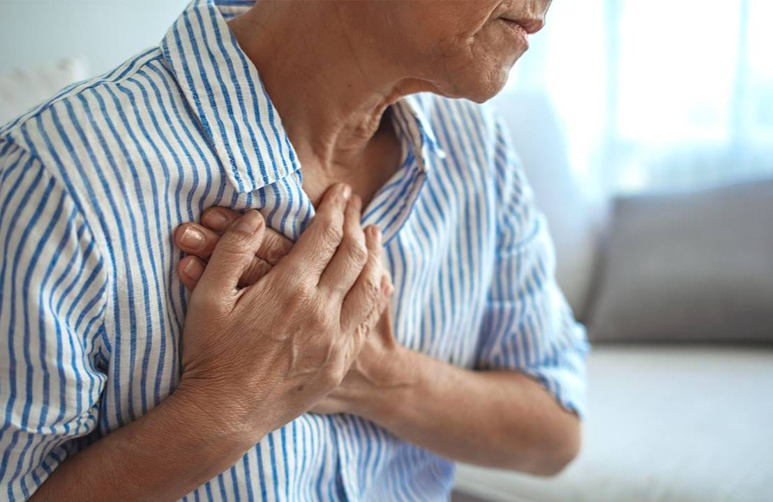 A middleaged woman grabbing her chest in pain. Ageism, heart disease, ageist, Next Avenue