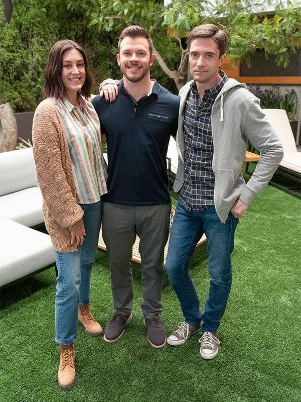 Three siblings standing arm in arm, smiling.