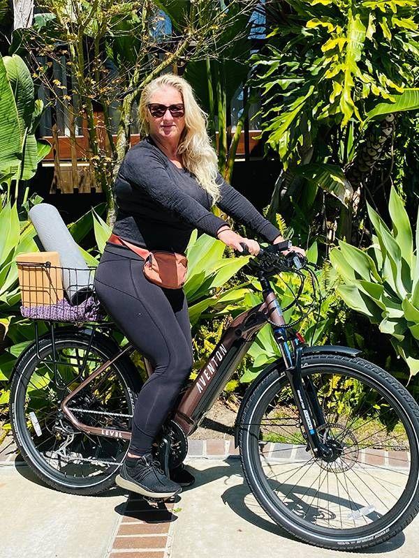 A woman sitting on an electric bike with a basket on the back. E bike, Next Avenue