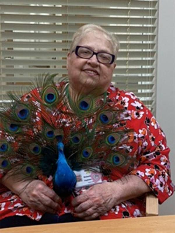 An older woman and PACE recipient holds a peacock statue. Home care, Next Avenue