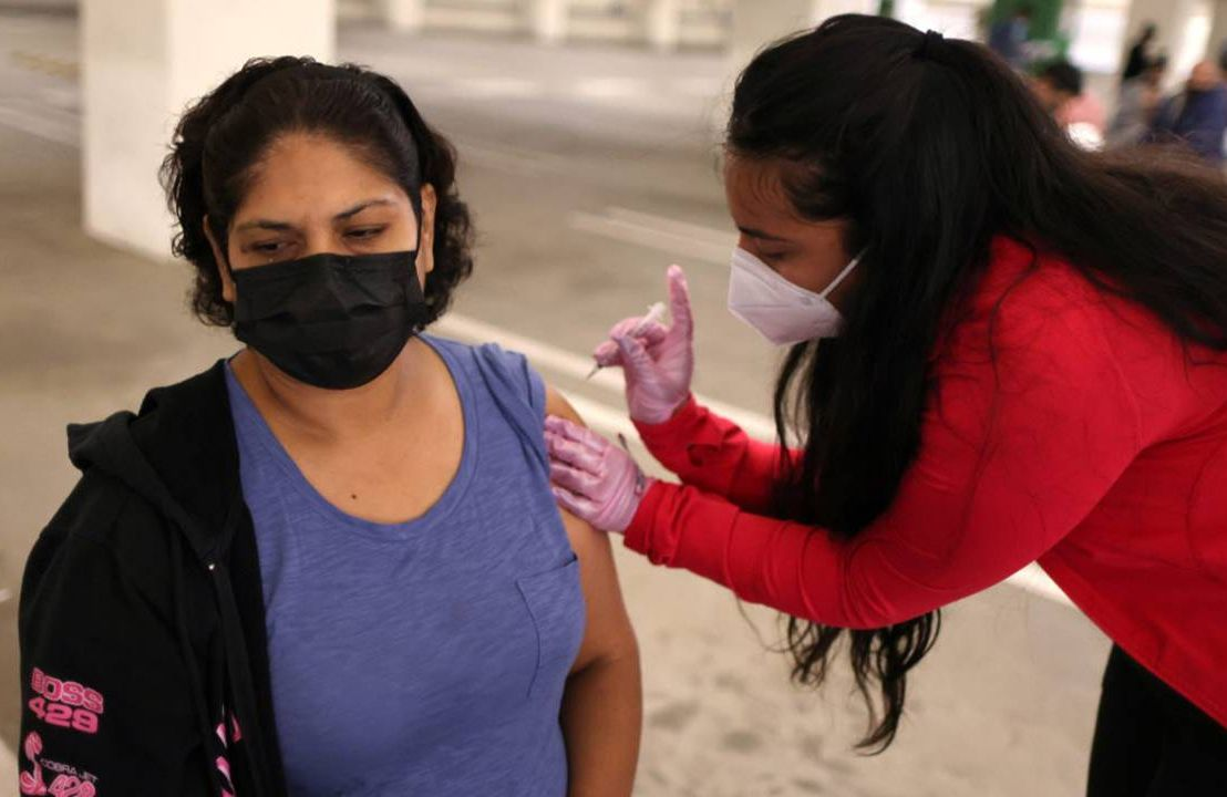 A woman wearing a purple T-shirt getting a COVID-19 vaccine. Women COVID-19 vaccine side effects, Next Avenue