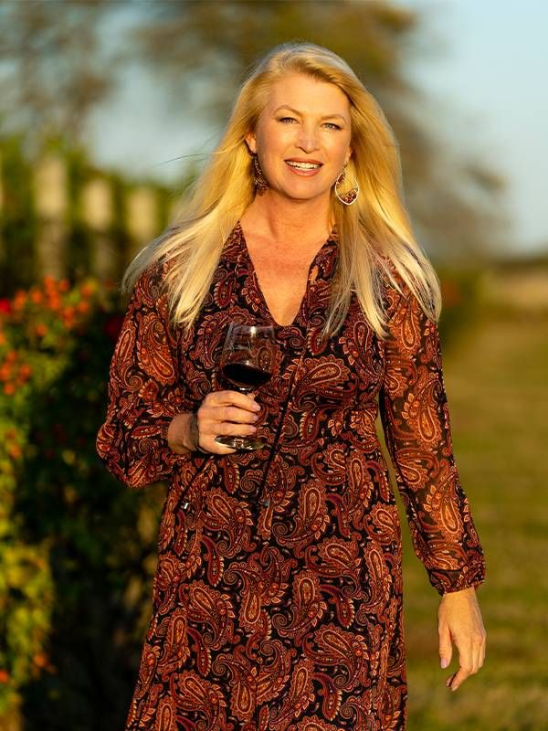 A woman walking outside holding a wine glass. Entrepreneurs, small business, Next Avenue