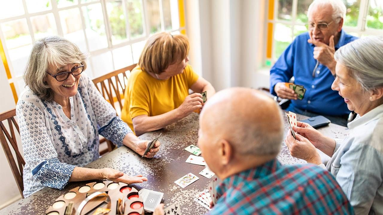 a group of older adults sit around a table talking