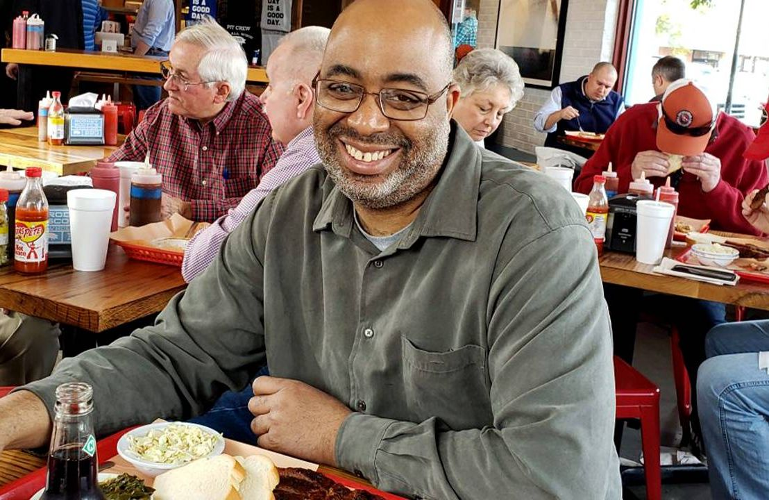 Author Adrian Miller at a BBQ restaurant smiling. barbecue, African American Black cooks, Next Avenue