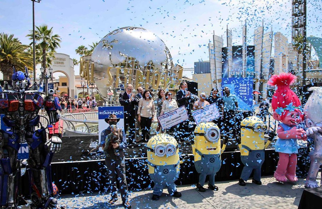 Confetti and costumed characters surround CA governor. Vaccine incentives, COVID-19, Next Avenue
