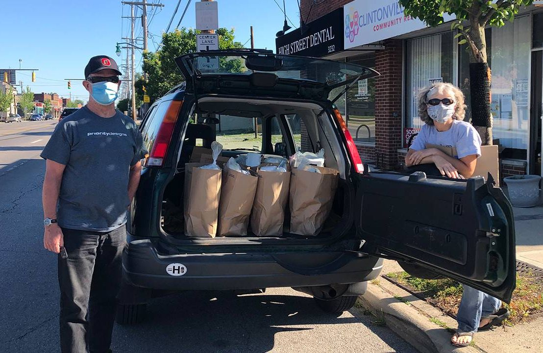 Two older adults standing in front of a car filled with groceries. Next Avenue, Villages Neighborhood Network