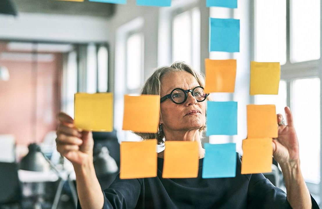 An older woman trying to make a plan using stickie notes. Career advice, Tapas life,Next Avenue