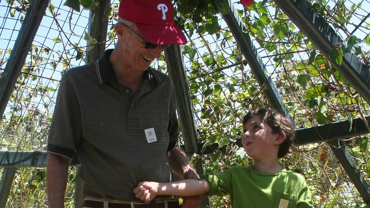 A grandfather and his grandson smiling in a garden. Dad, books, Next Avenue