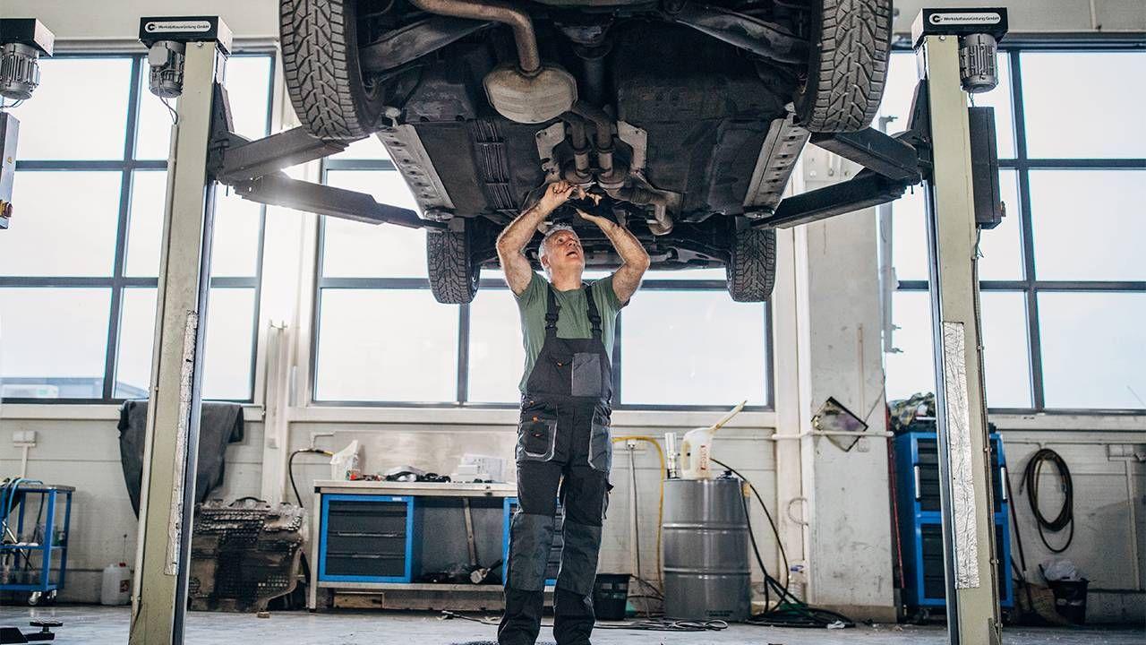 A mechanic fixing a car in the auto shop. Next Avenue, car insurance