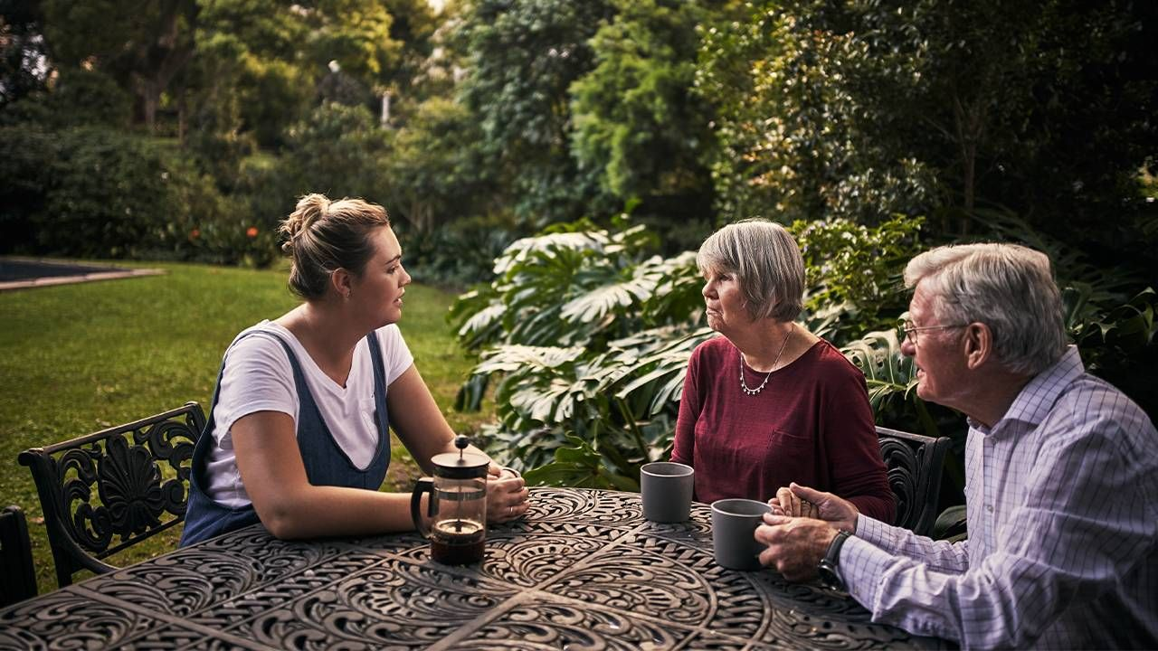 An adult child talking with her parents outside. communication, aging parents, Next Avenue
