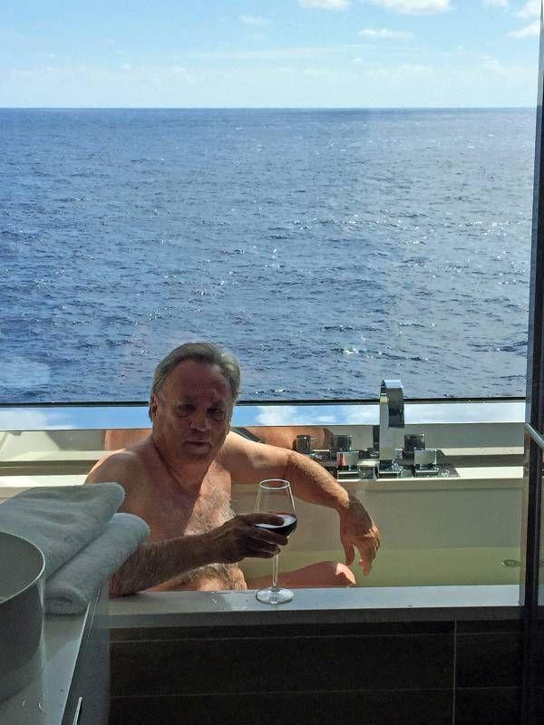 A man sitting in a bathtub holding a glass of wine. Cruise, trip, travel, Next Avenue