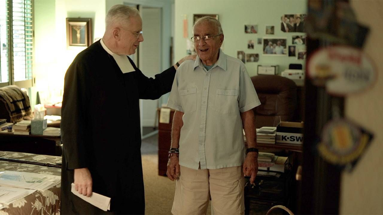 A priest and an older man standing next to eachother. Caregiver, Next Avenue, It's not a burden, caregiving