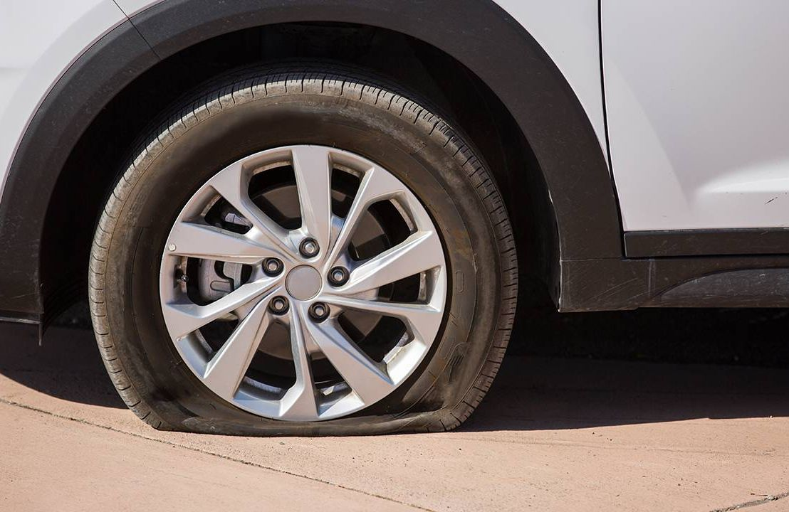 A closeup of a car with a flat tire on the road. First flat tire, Next Avenue