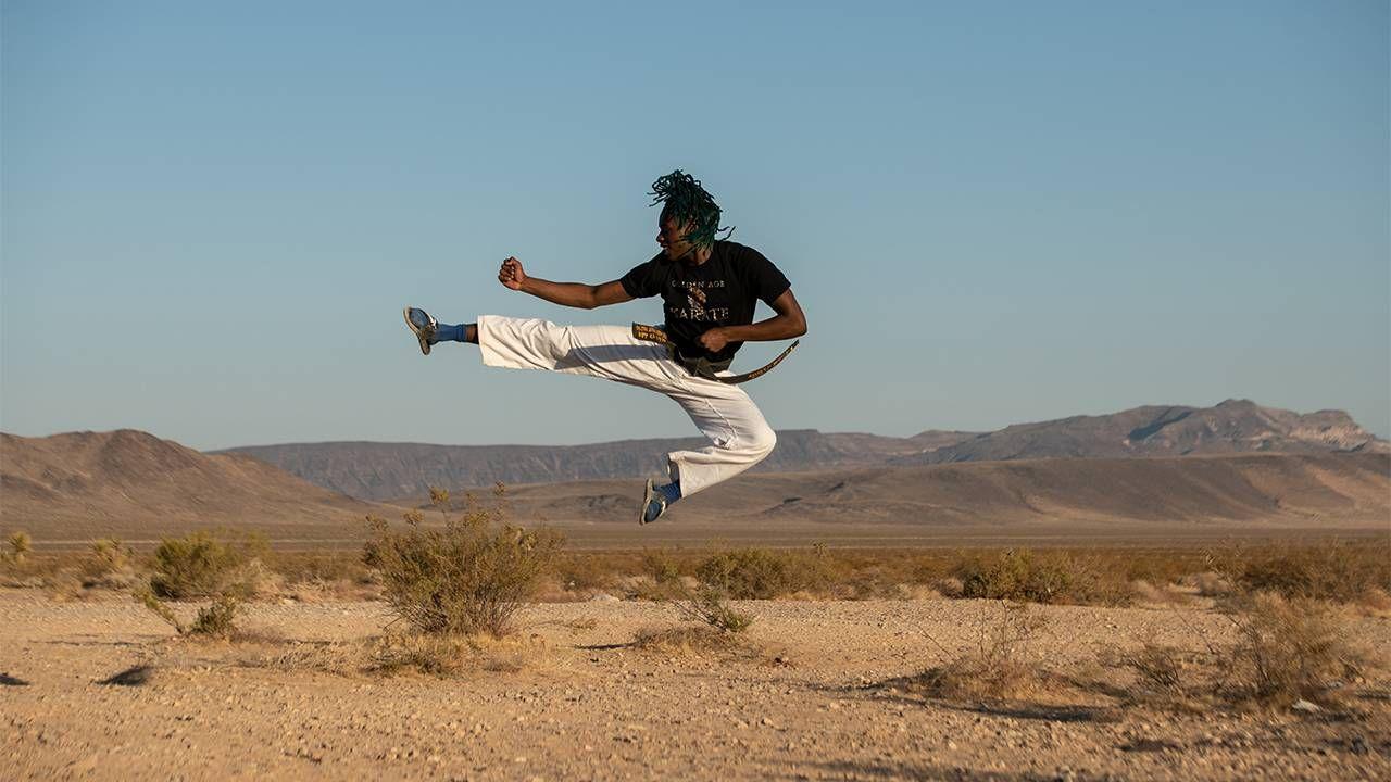 A man doing a high karate kick in the desert. UnLonely Film Festival, Next Avenue