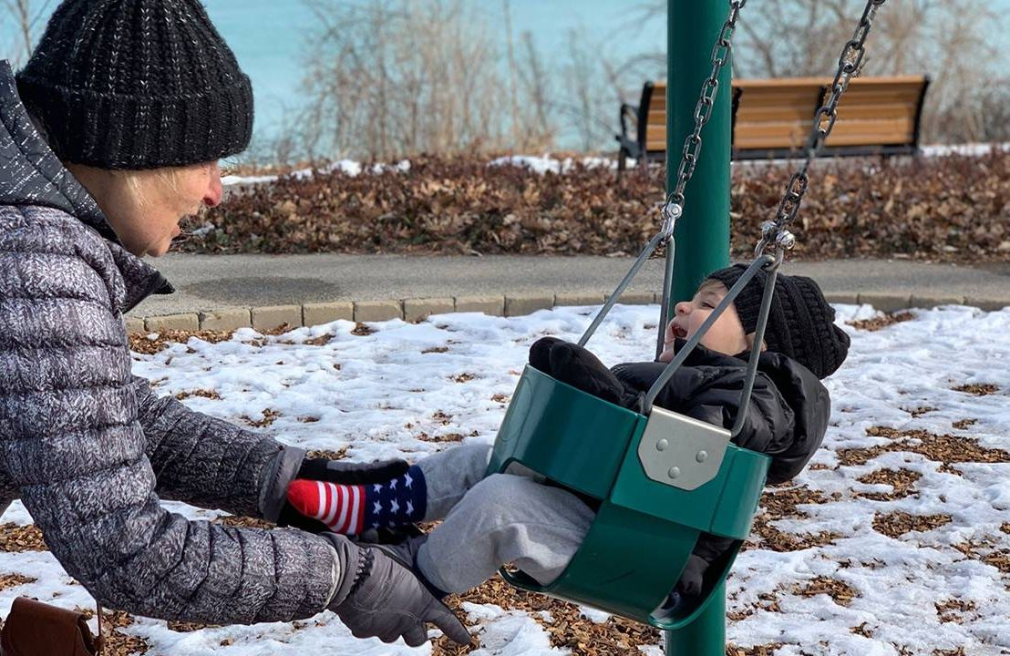 A grandparent pushing a grandchild on the swing. Picture, photo, grandparents, grandmother,Next Avenue