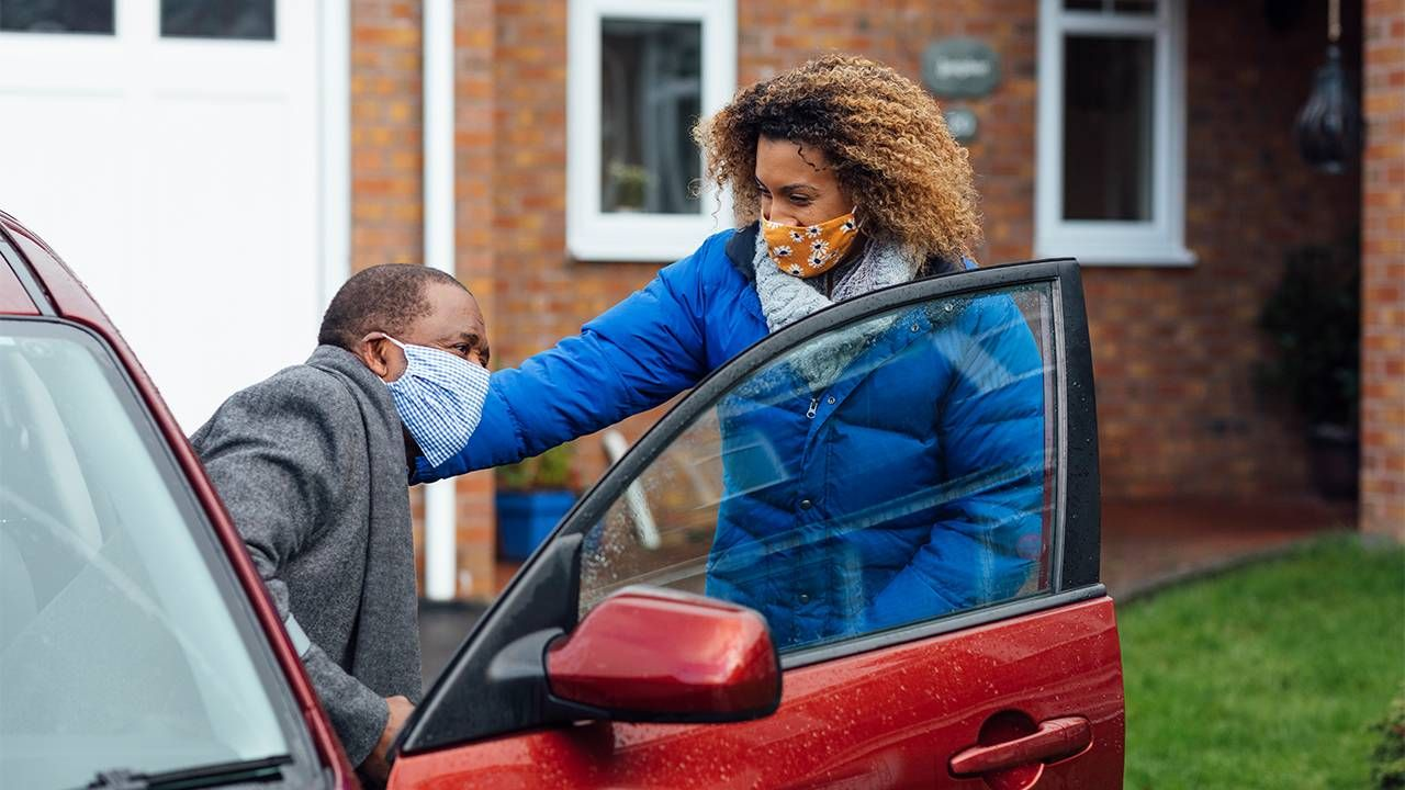 An adult daughter helping her older father into the car. Guardianship, Next Avenue, eldercaring coordination
