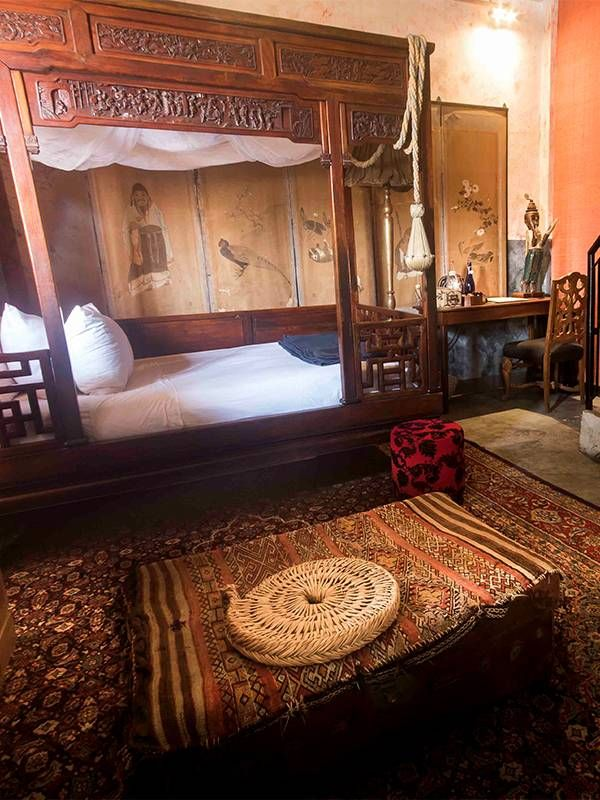 Interior bedroom with ornate wooden bedframe. second-act business, Cambodia, Next Avenue