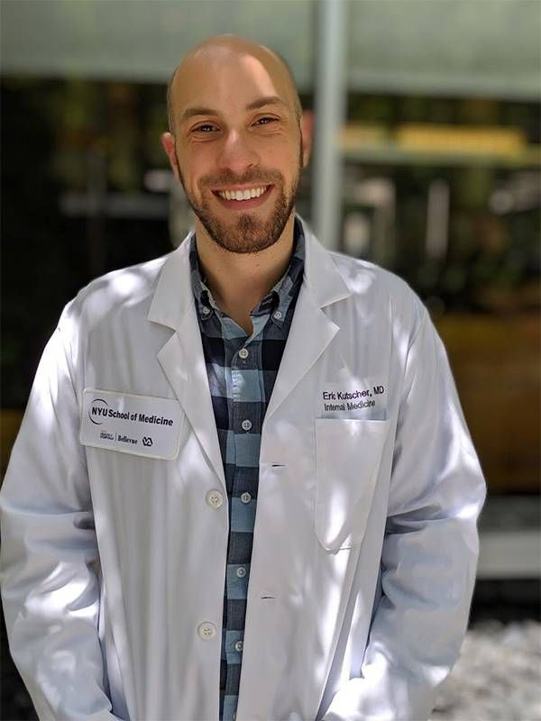 A doctor wearing a white coat, smiling. COVID-19, survivor's guilt, Next Avenue