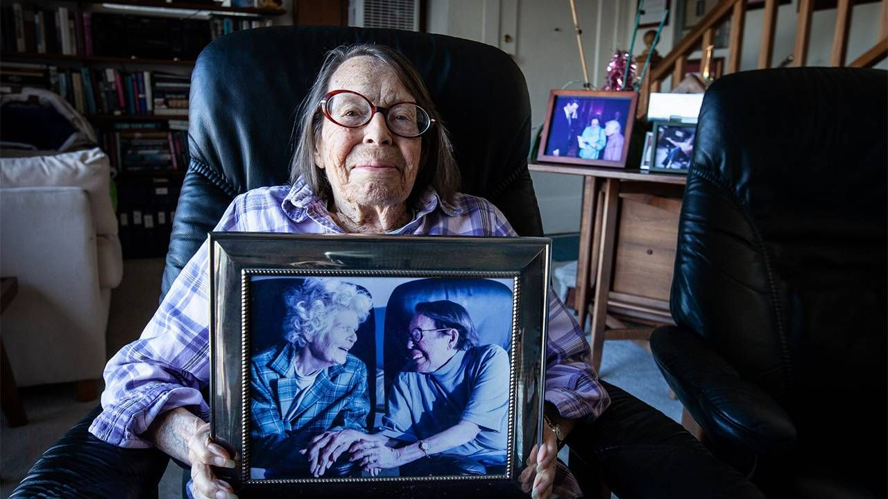 The LGBTQ activist holdng a framed photo of her and her wife.  Lyon Martin house, lesbian activists, Phyllis Lyon, Del Martin, Next Avenue