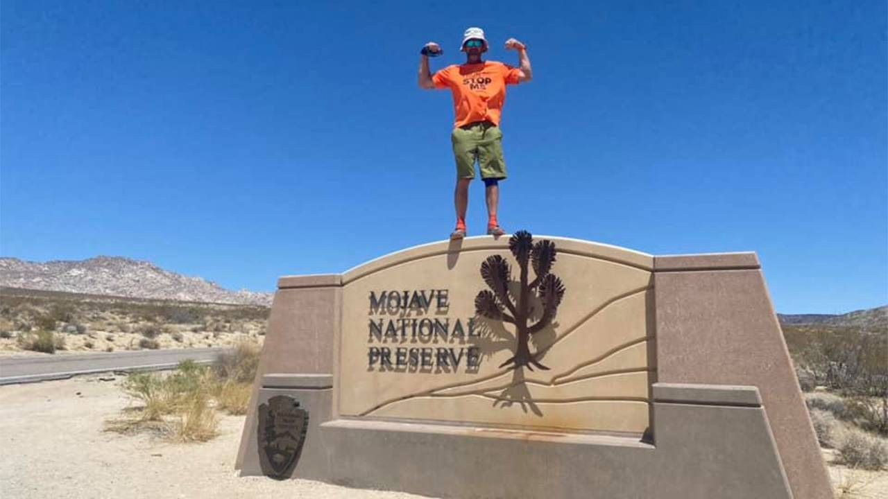 "A man standing on top of a large ""Mojave Desert"" landmark. Running, Next Avenue"