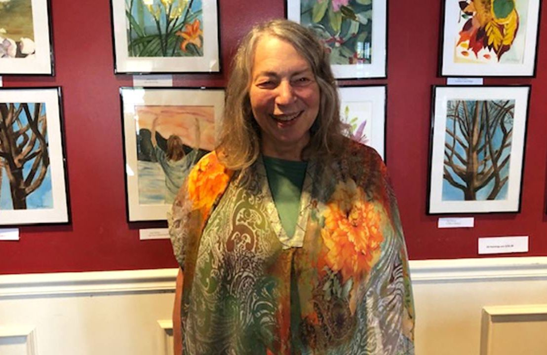 Joan Ditzion standing in front of several of her artworks. Next Avenue, Our Bodies Ourselves