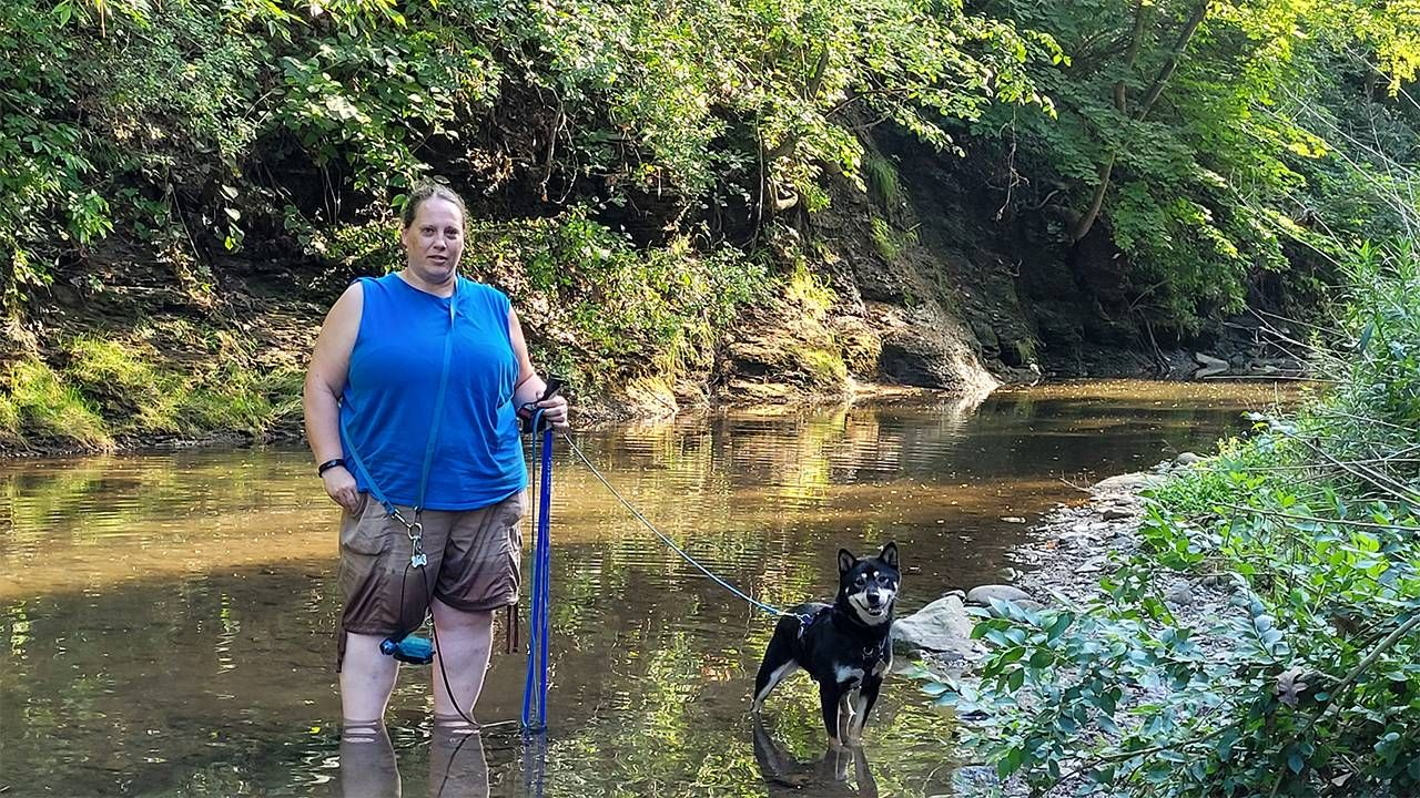 A woman and her dog standing in a creek. Dogs, aging, Next Avenue