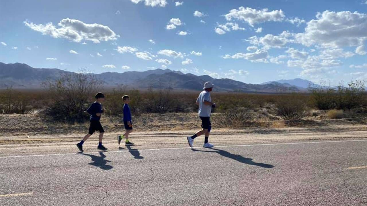 A man running on a desert road with kids behind. Next Avenue