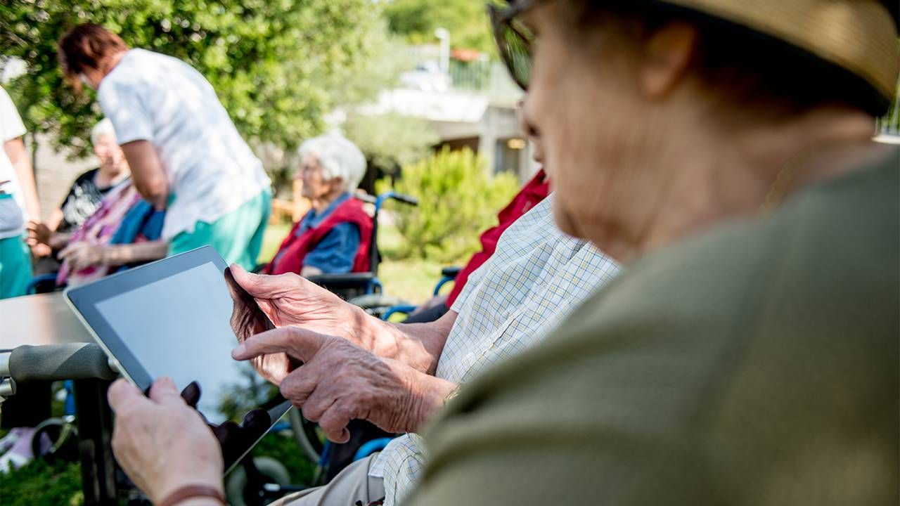 older adults at a nursing home using an ipad to connect.