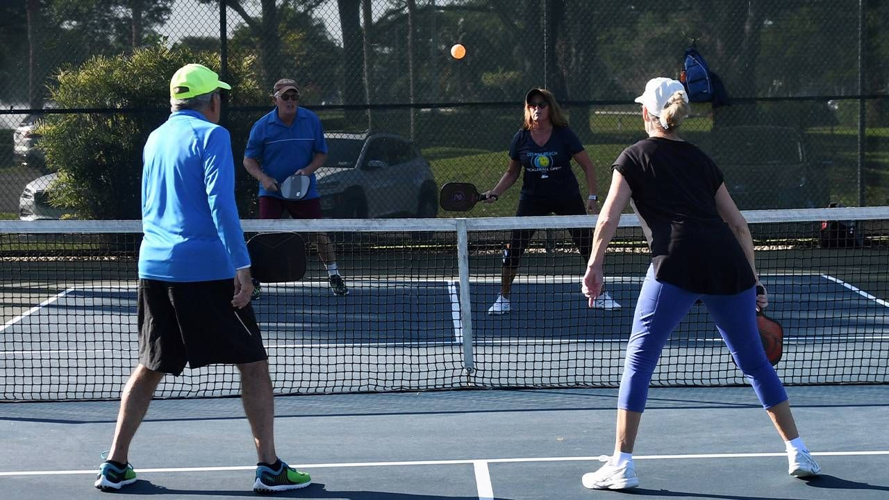 A group of people playing pickleball outside. Next Avenue