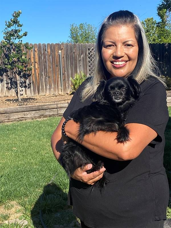 A woman holding a little black dog in her backyard. Next Avenue, Black and Latina women, COVID-19 pandemic