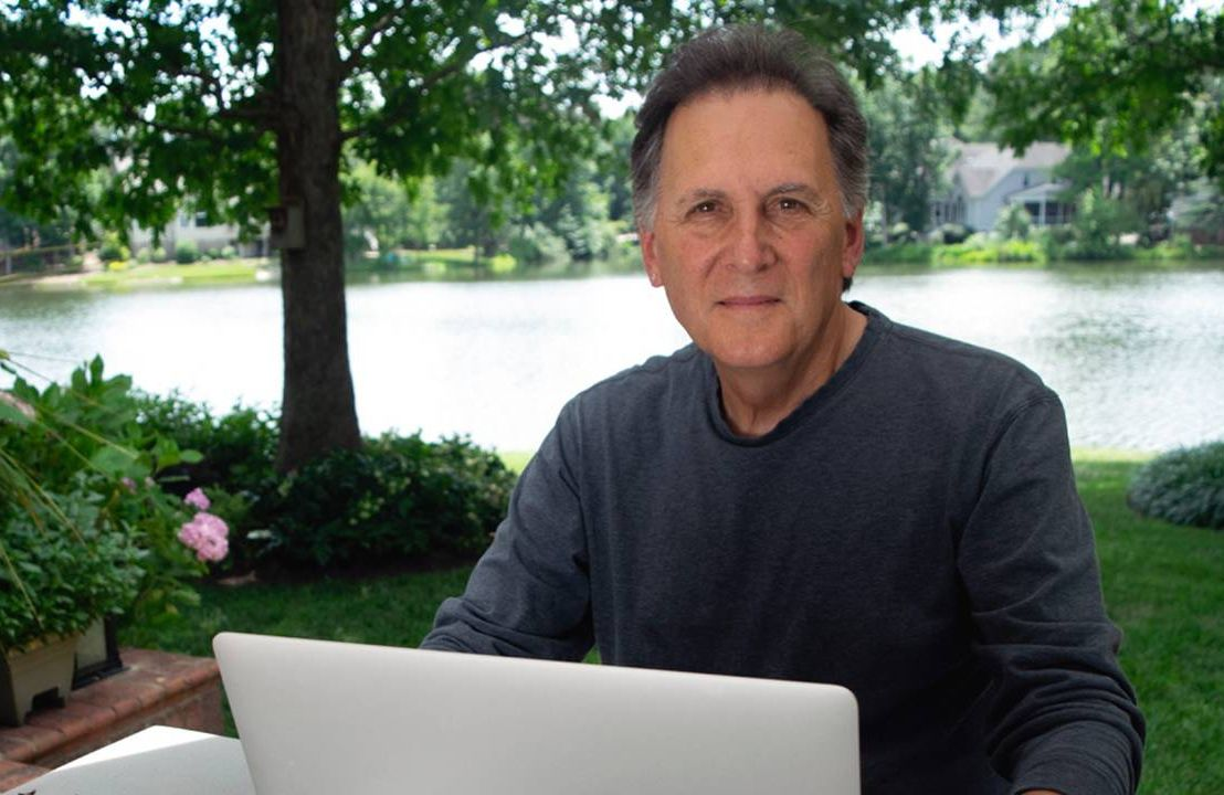 A man with a laptop sitting outside. Ageism in Hollywood, Age Inclusion in Media, Next Avenue