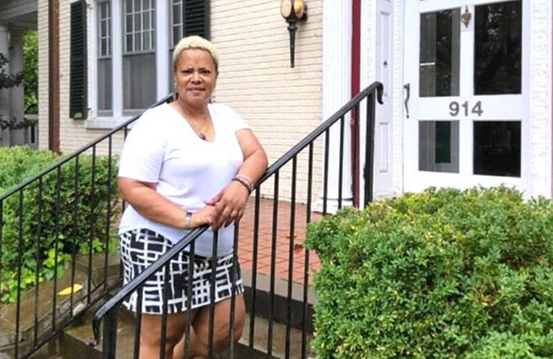 A woman standing on the front steps of a B&B. Next Avenue, Black and Latina women, COVID-19 pandemic