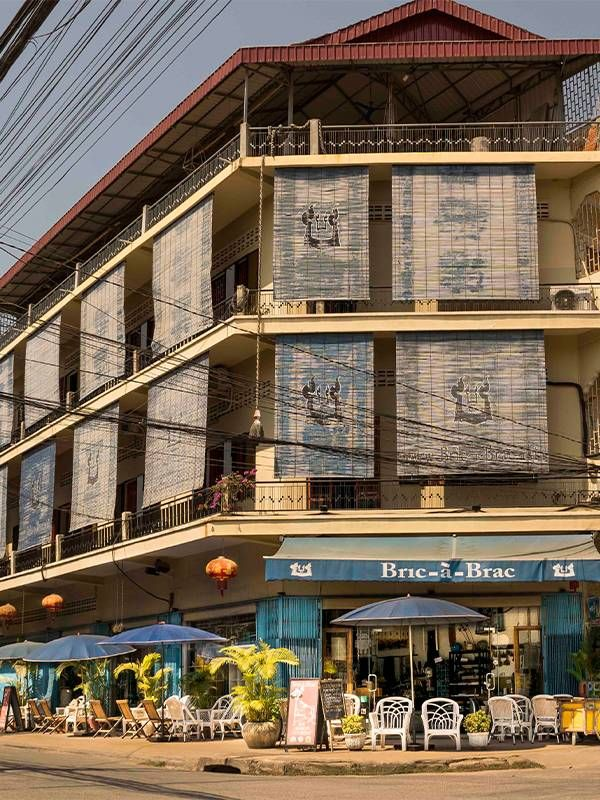 The exterior of a B&B in cambodia with a cafe below, palm trees. Second-act business, Cambodia, Next Avenue