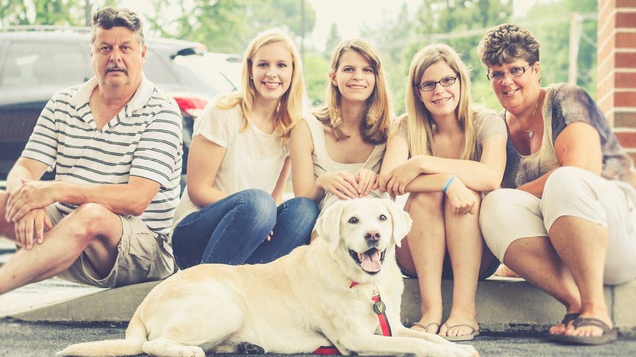 A family and their dog sitting on a curb. COVID-19, survivor's guilt, Next Avenue