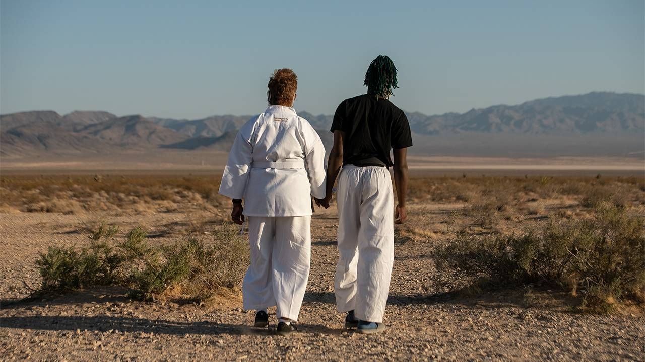 A grandson and his grandma walking in the desert wearing karate gear. Next Avenue