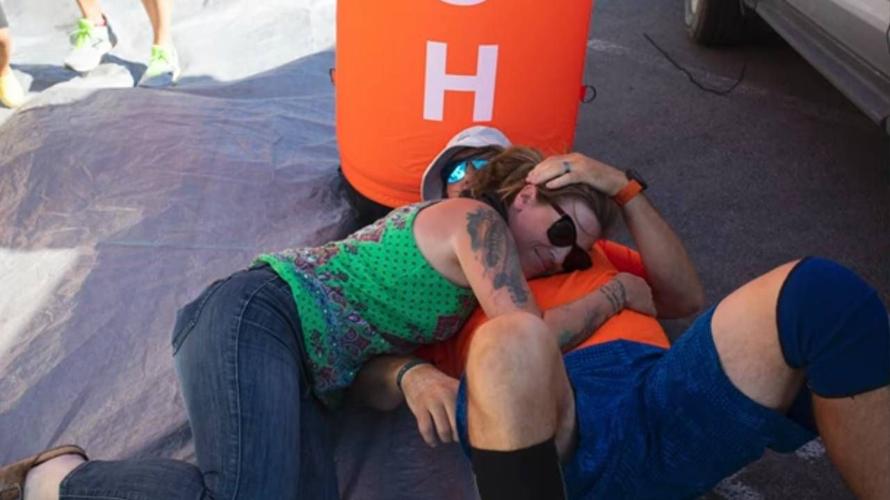 A man hugging his wife laying down at the finish line. Running, Next Avenue