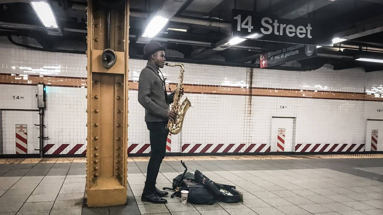 A saxophone player at the 14th Street subway stop. photography, photographer, Next Avenue