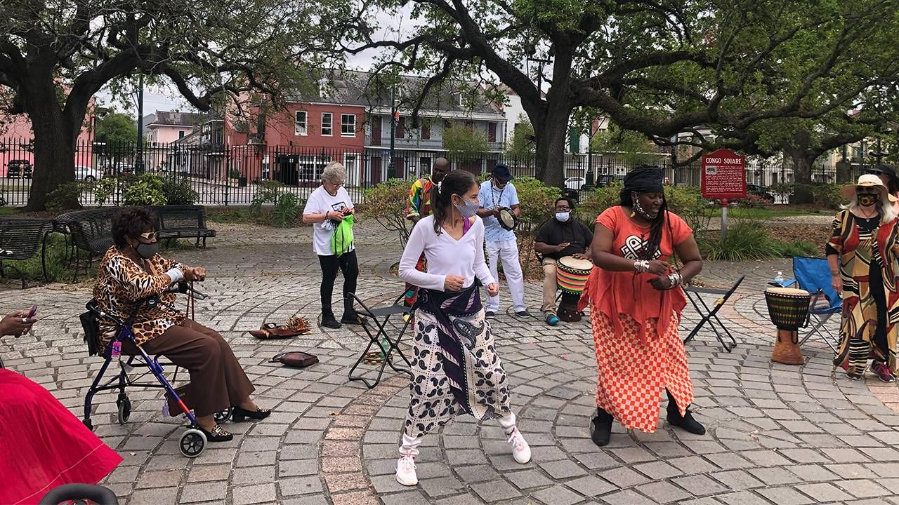 A group of people dancing with drums outside. Mardi Gras Indians, dancing, Next Avenue